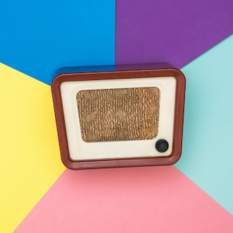 Radio retro sobre un fondo de varios colores. ingeniería de radio del tiempo pasado. diseño retro. la vista desde arriba.