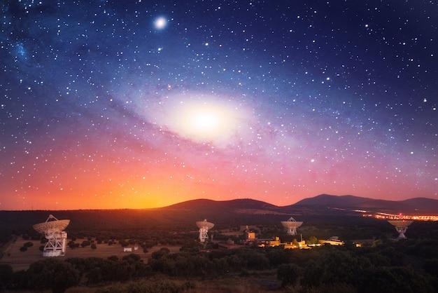 Radio telescopios nocturnos con galaxia en el cielo.