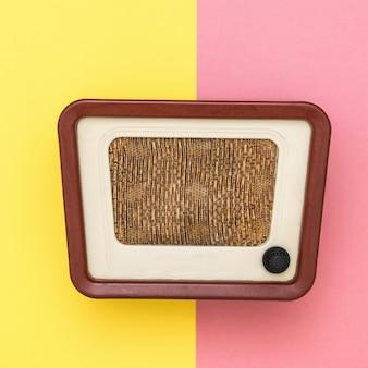 Radio vintage con asa redonda sobre pared amarilla y rosa. ingeniería de radio del tiempo pasado. la vista desde arriba.