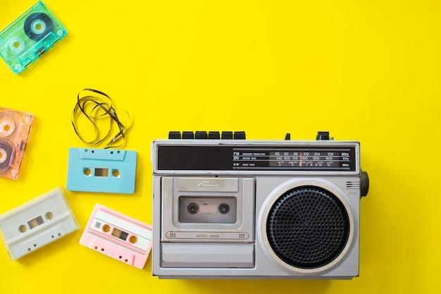 Radio vintage y reproductor de casete sobre fondo amarillo