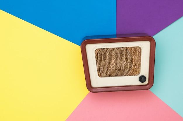 Radio vintage sobre una superficie de seis colores. ingeniería de radio del tiempo pasado. diseño retro. la vista desde arriba.