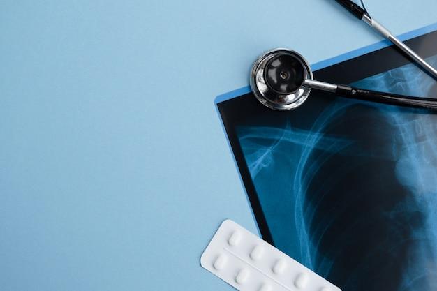 Radiografía, estetoscopio médico y pastillas en azul