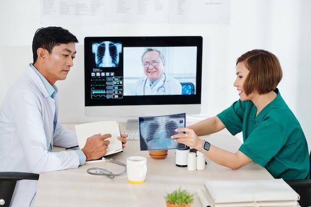 Radiólogo mostrando radiografías de pulmones a colega en reunión en línea con oncólogo experimentado
