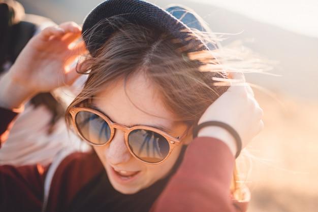 Una ráfaga de viento sopla el sombrero de las chicas