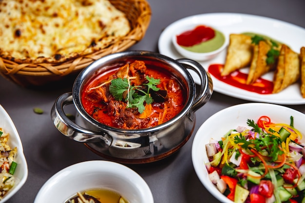 Ragú de cordero lateral con cebolla frita, zanahoria, salsa de tomate, verduras y ensalada de verduras sobre la mesa