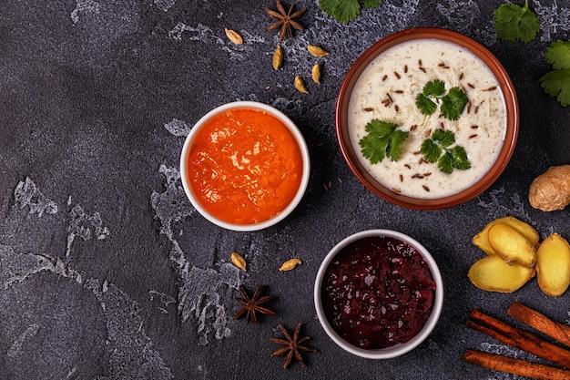 Raita india tradicional con salsas de pepino, comino, cilantro y chutney