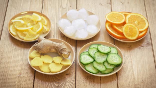 Raíz de jengibre, limón, pepino, hielo sobre un fondo de arpillera.