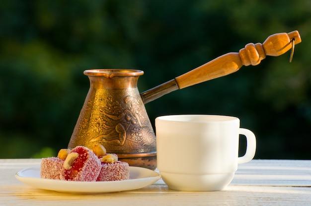 Rakhat lokum, cezve y una taza de café a la luz del sol