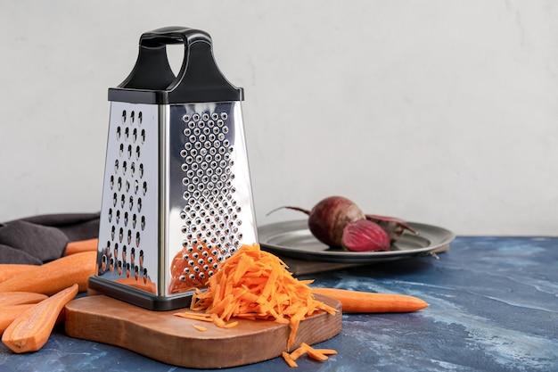 Rallador de metal y verduras en la mesa de la cocina