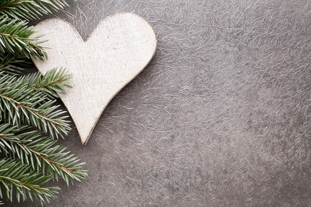 Rama de abeto con adornos navideños sobre un fondo gris.
