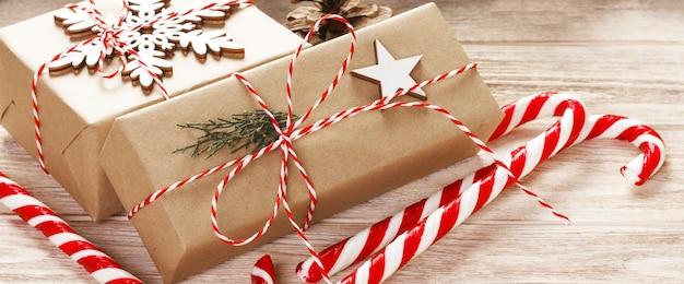 Rama de abeto con caja de regalo de navidad y bastones de caramelo en madera