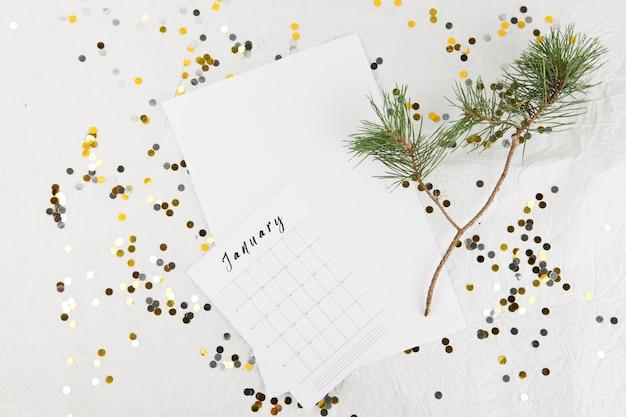 Rama de abeto con calendario de enero en mesa