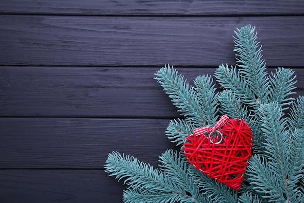 Rama de árbol de abeto con un corazón rojo sobre fondo negro.
