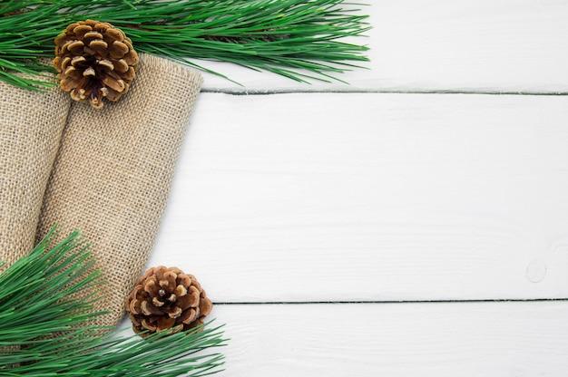 Rama de árbol de navidad y cono en arpillera sobre superficie vintage de madera blanca
