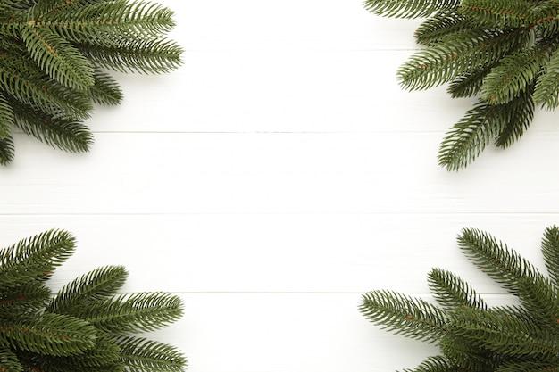 Rama de un árbol de navidad en la mesa de madera blanca.