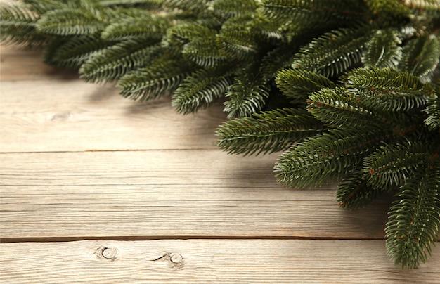 Rama de un árbol de navidad en la mesa de madera gris.