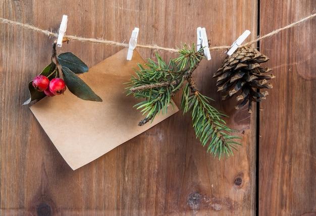 Rama de árbol de navidad, piña y bayas de invierno en una cuerda con pinzas para la ropa. deseando una feliz navidad