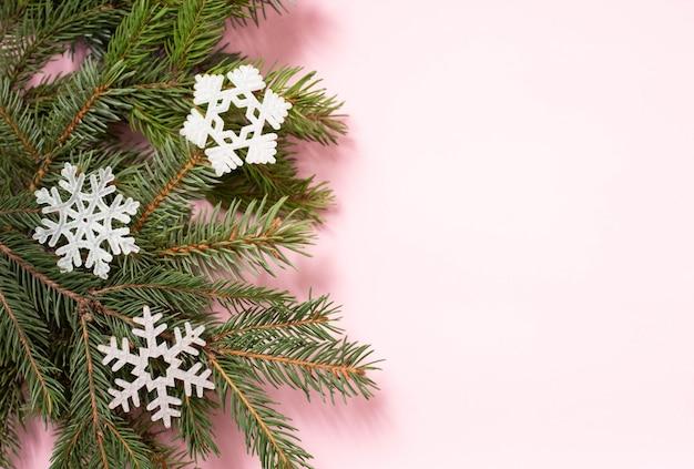 Rama de árbol de navidad con tres copos de nieve blanca sobre fondo rosa con espacio de copia