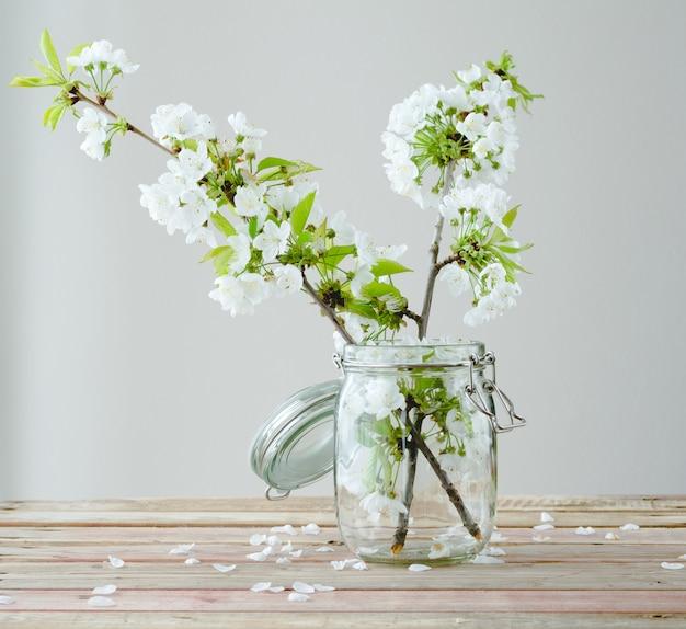 Rama de cerezo con flores en frasco de vidrio en madera