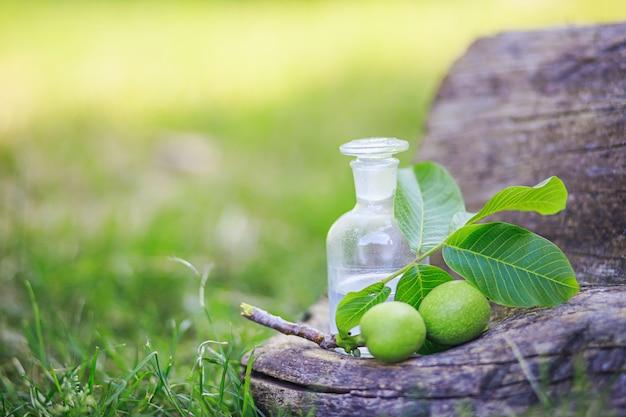 Rama con dos nueces verdes inmaduras con hojas para la preparación de medicamentos y tinturas. botella transparente con elixir de corcho. botella de medicina