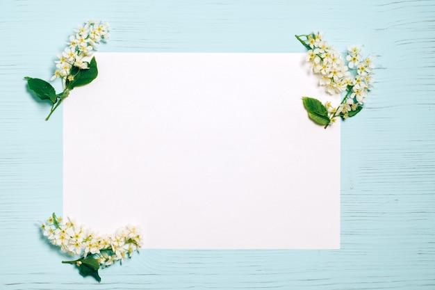 Rama de la flor del cerezo del pájaro en la mesa blanca y de madera
