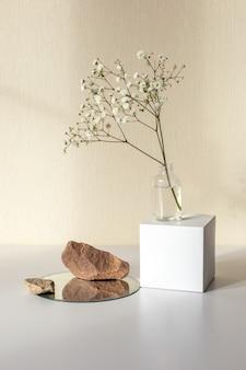 Una rama de una flor de gypsophila blanca de pie sobre una botella en un cubo de papel blanco