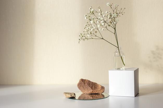 Una rama de una flor de gypsophila blanca de pie sobre un cubo de papel blanco y piedras