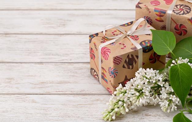 Una rama de flor lila blanca y caja sorpresa en un embalaje festivo. fondo de madera, tiro del estudio.