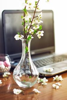 Rama de flores de primavera y coloridos huevos de caramelo rosa para pascua