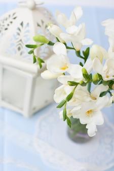 La rama de fresia blanca con flores y capullos en botellas decorativas.