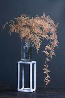 Rama de helecho de espárragos o setaceus de espárragos pintados en oro en un jarrón de vidrio sobre un soporte geométrico de metal, fondo festivo o concepto