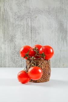 Rama de jugosos tomates en una pieza de corte de madera vista lateral sobre una superficie sucia gris y blanca