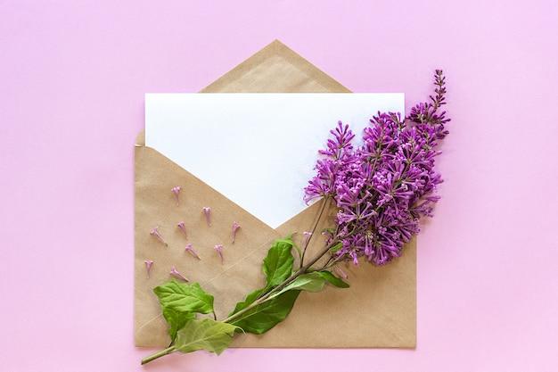 Rama de lila en sobre artesanal con tarjeta vacía.