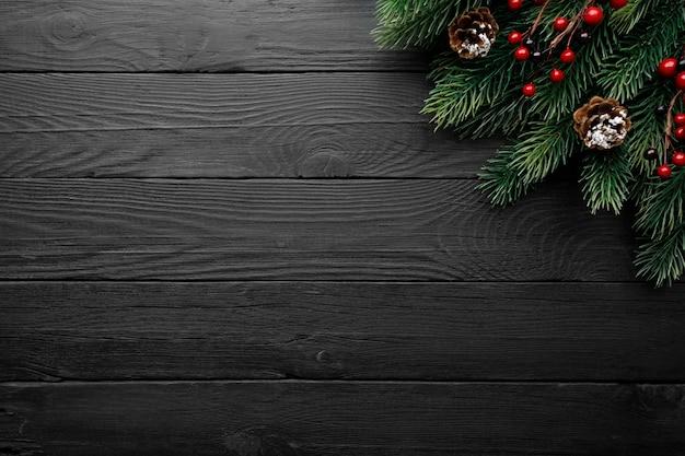 Rama de pino con frutos rojos y conos sobre una mesa de madera negra