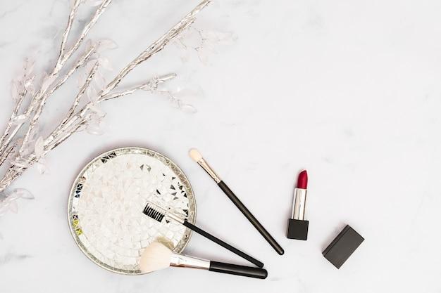 Rama de plata y cristal con placa; pinceles de maquillaje y lápiz labial sobre fondo blanco