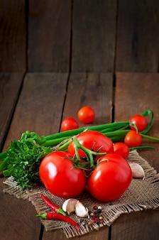 Rama de tomate fresco sobre fondo de madera