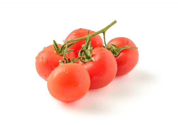 Rama de tomates maduros sobre un fondo blanco.