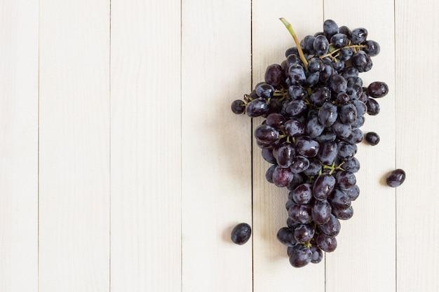 Rama de uva negra sobre madera blanca