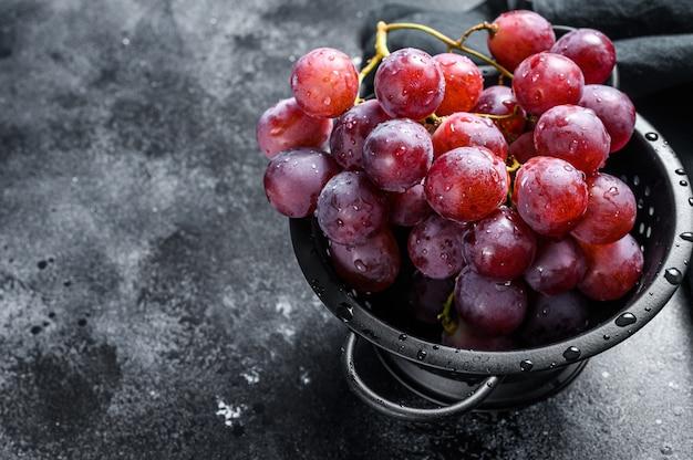 Rama de uvas rojas jugosas en un colador. fondo negro.