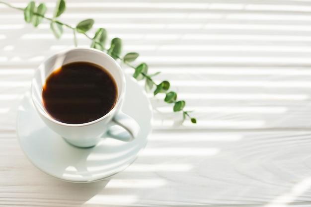 Rama verde del eucalipto y taza de café sabrosa en el escritorio de madera blanco