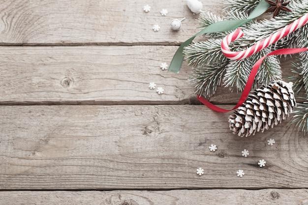 Rama verde de navidad y regalos en la pared de madera