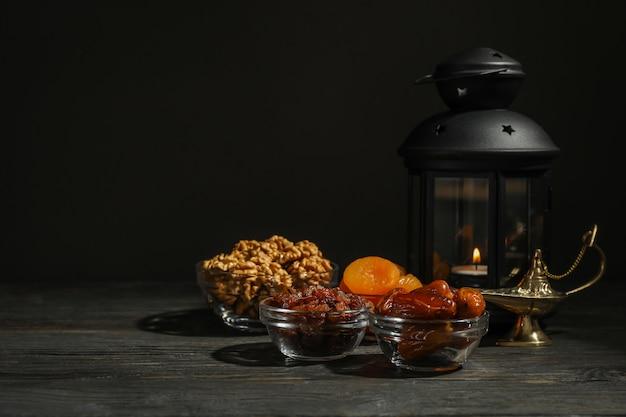 Ramadan kareem comida y decoración en mesa de madera sobre fondo oscuro