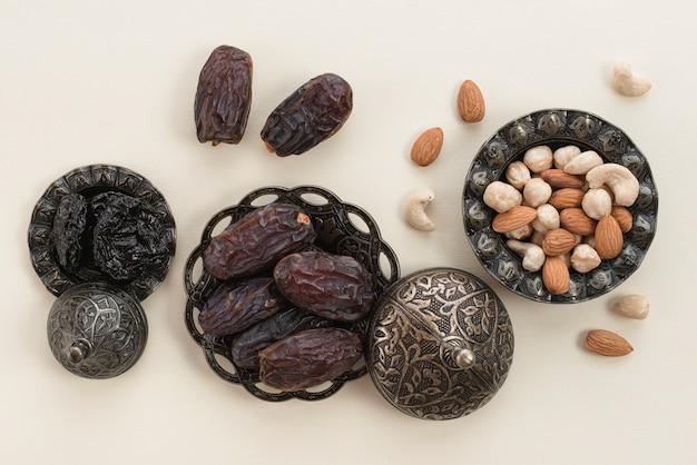 Ramadán kareem con fechas premium y nueces sobre fondo blanco