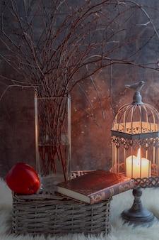 Ramas de abedul en un jarrón, un candelabro con una vela, un libro y una manzana roja sobre un fondo gris.
