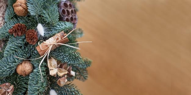 Ramas de abeto con adornos navideños sobre fondo de madera, copyspace