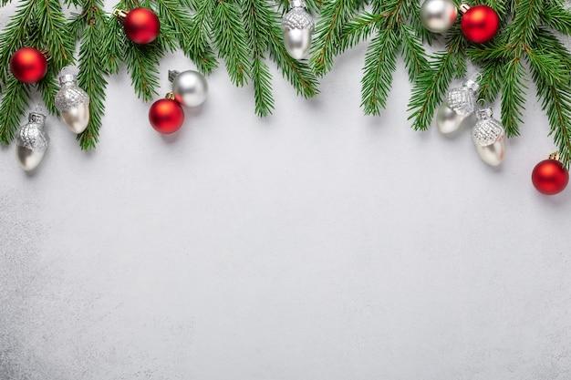 Ramas de abeto con bolas de navidad rojas y plateadas sobre fondo blanco.