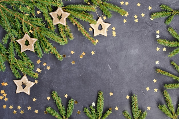Las ramas de abeto, decoración de estrellas de madera, confeti dorado en la oscuridad