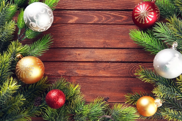 Ramas de abeto de navidad con juguetes en mesa de madera