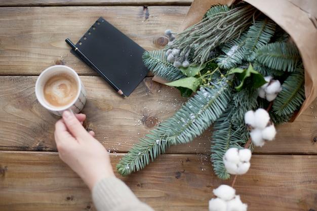 Ramas de abeto en papel marrón, cuaderno negro y taza de café