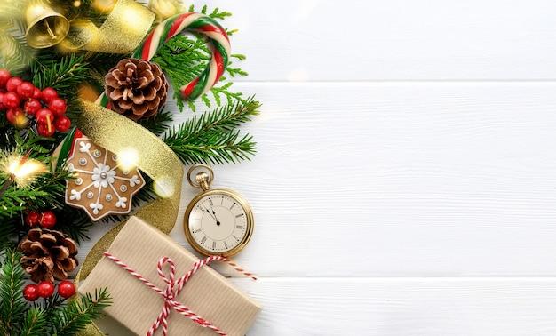 Ramas de abeto, reloj de estilo retro, adornos navideños y regalo sobre fondo blanco de madera. últimos momentos antes de navidad o año nuevo. vispera de año nuevo. vista superior. copia espacio